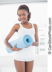 Beautiful woman posing with exercise mat