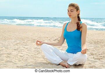 Beautiful woman practice yoga on the beach