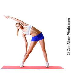 Beautiful woman practices aerobics in studio, isolated on...
