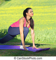 Beautiful woman practices yoga in nature against the yellow field