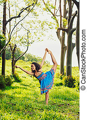 Beautiful Woman Practicing Yoga Outside in Nature