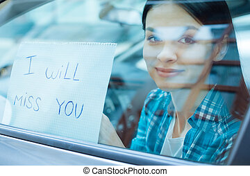 Beautiful woman pressing a farewell note to car window -...