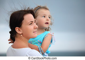 beautiful woman protects little girl from wind on seacoast