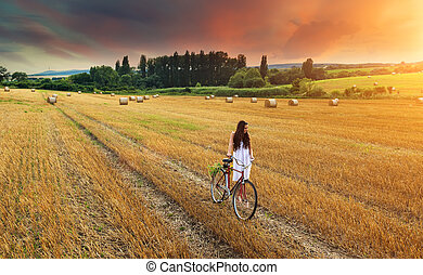 Beautiful woman pushes old red bike in a wheat field