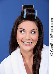 Beautiful woman putting rollers in her hair