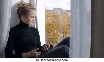 Beautiful woman reading a book in e-reader sitting on a windowsill