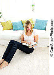Beautiful woman reading a book in the living-room