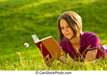 Beautiful woman reading a book in the park