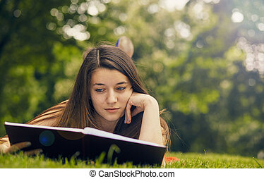 Beautiful woman reading book in nature