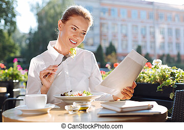 Beautiful woman reading documents while eating out - Good at...