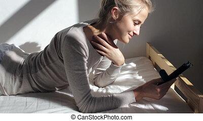 Beautiful woman reading ebook - Beautiful caucasian blonde...