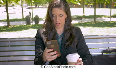 Beautiful woman reading mobile phone app technology on park...