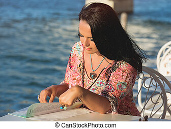 Beautiful woman reading the menu at a Greek  seaside restaurant