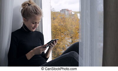 Beautiful woman reads e-book sitting on windowsill