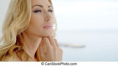 Beautiful woman recalling memories at the seaside