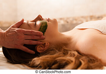 Beautiful woman receiving a facial massage in a spa. -...