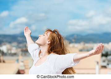 Beautiful woman rejoicing in the sunshine standing with her...