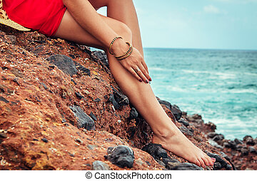 Beautiful woman relaxes sitting on the rock by the sea. Closeup of female legs.