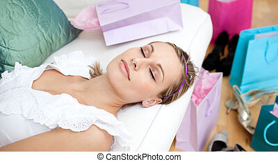 Beautiful woman relaxing after shopping surrounded with...