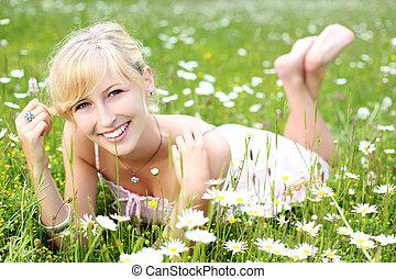 Beautiful woman relaxing amongst daisies