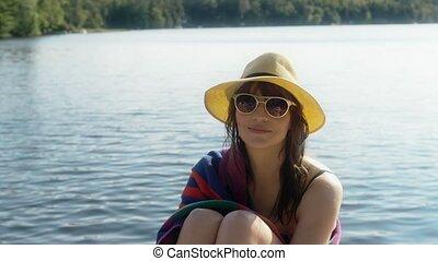 Beautiful woman relaxing by the water. 4K UHD.
