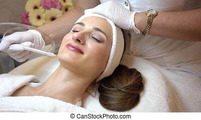 Beautiful woman relaxing during non-invasive facial...