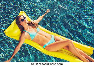 Beautiful Woman Relaxing Floating on Raft in Pool