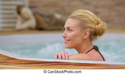Beautiful woman relaxing in a hot tub. Happy woman relaxing...
