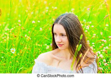 Beautiful woman relaxing in green grass