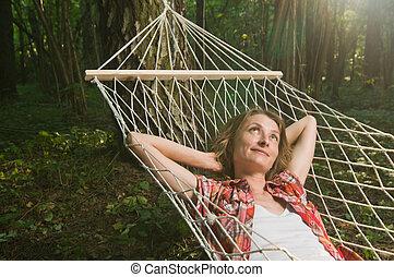 Beautiful woman relaxing in hammock