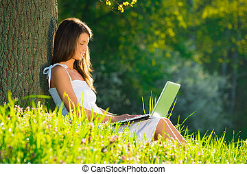 Beautiful woman relaxing on grass with laptop