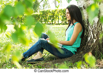 Beautiful woman relaxing outdoors on grass about tree