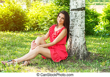 Beautiful woman relaxing outdoors on grass looking happy and smiling.