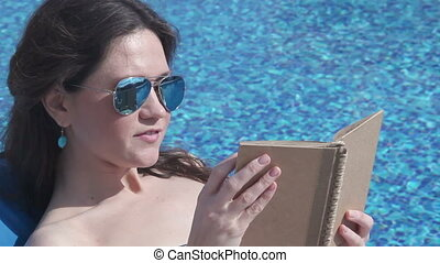 Beautiful woman relaxing with book by pool, sunbathing at beach