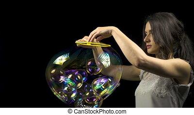 Beautiful woman releasing soap bubbles
