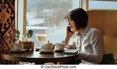 Beautiful woman resting during lunch, sitting in a cafe. Business lunch. Slow motion