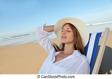 Beautiful woman resting in deckchair at the beach