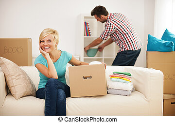 Beautiful woman resting on couch while her husband decorating their new living room
