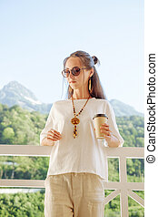 Beautiful woman resting with cup of coffee on balcony in front of mountains.