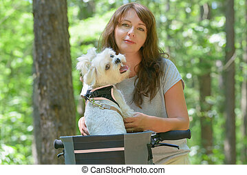 Beautiful  woman riding a bike with her dog