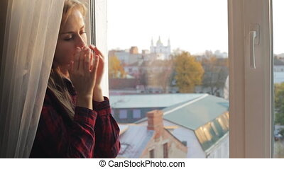 Beautiful woman rubs her dry eyes near the window -...