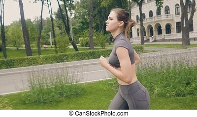 Beautiful woman running at morning jog while cardio training...