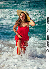 Beautiful woman runs away from waves on the beach