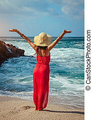 Beautiful woman runs away from waves on the beach. Girl relaxing and enjoying freedom on vacation