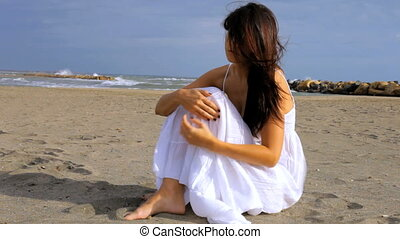 Beautiful woman sad on the beach wi