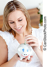Beautiful woman saving money in a piggy-bank