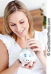 Beautiful woman saving money in a piggy-bank