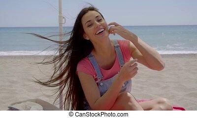 Beautiful woman seated in shade at beach - Single beautiful...