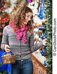 Beautiful Woman Selecting Christmas Ornaments