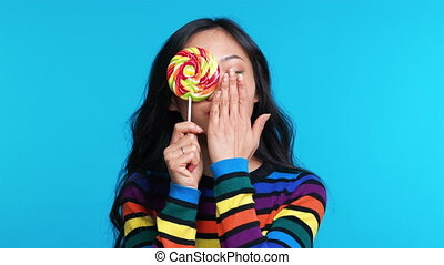 Beautiful woman send air kiss and cover her eye with colorful lollipop isolated on blue background. Emotions concept, sweet food